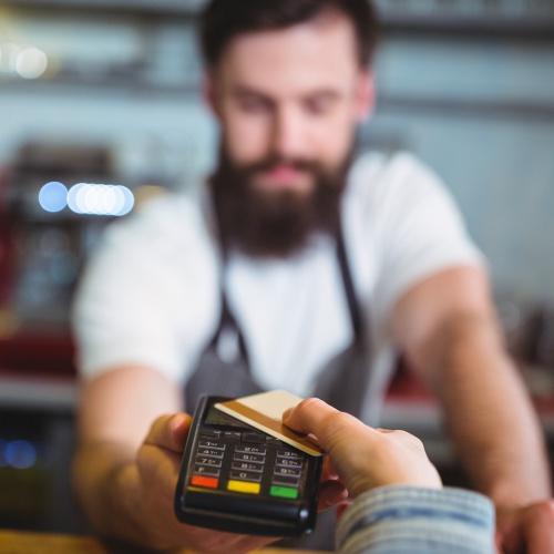 Customer making payment through payment terminal at counter